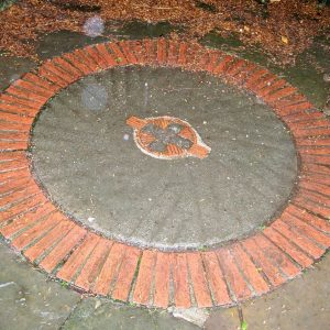 Millstone set in the path by the lychgate